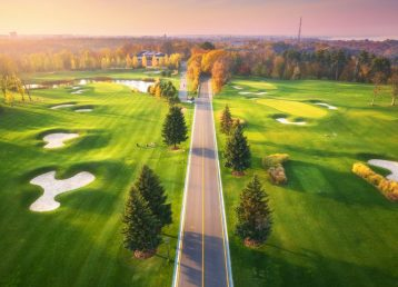 Road through the golf course at sunset in autumn. Aerial view