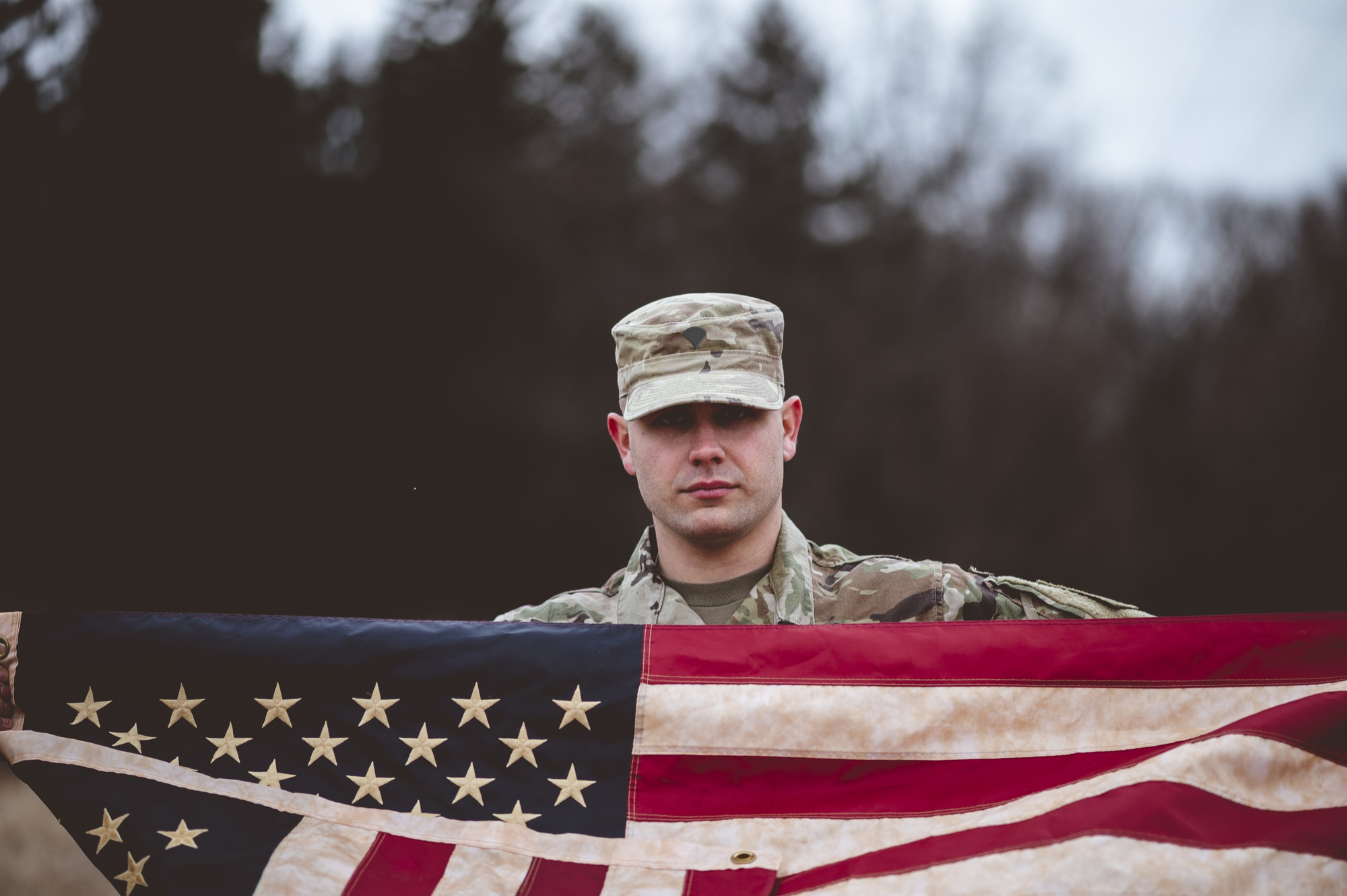 shallow-focus-shot-american-soldier-holding-american-flag