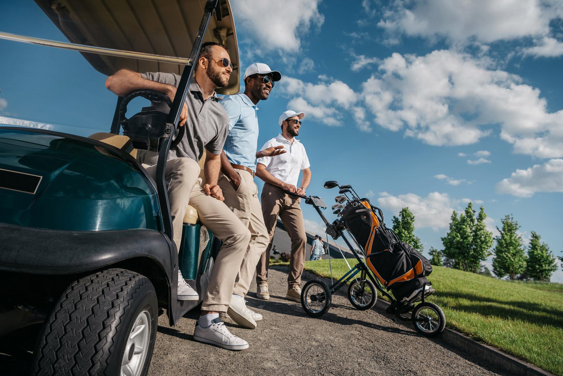 group-of-smiling-friends-standing-near-golf-cart-a-5V97KE9