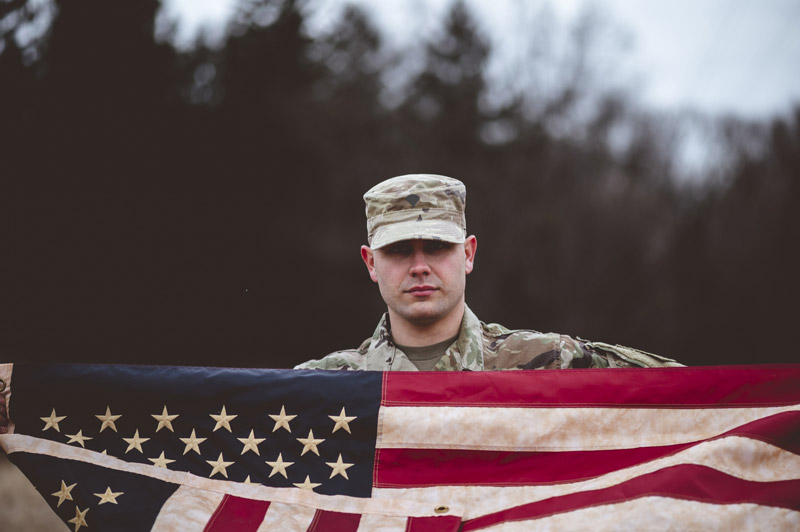 shallow-focus-shot-american-soldier-holding-american-flag-(1)